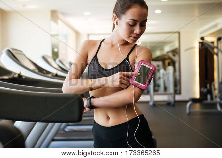 Image of young pretty sports lady make sport exercises indoors at gym while listening music and using phone.