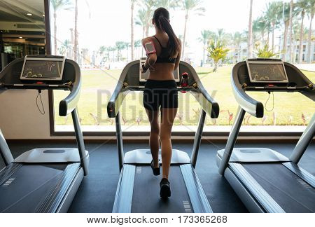 Back view image of young attractive fitness woman make sport exercises indoors at gym.