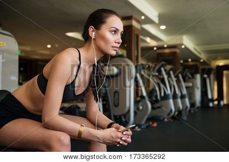Image of young pretty sports lady sitting indoors at gym while listening music and chatting by phone.