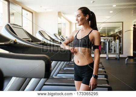 Image of young sports lady make sport exercises indoors at gym while listening music and posing.