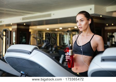 Picture of young sports lady make sport exercises indoors at gym while listening music. Holding water.
