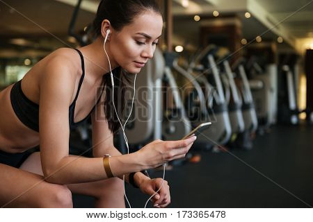 Photo of young amazing sports lady sitting indoors at gym while listening music and chatting by phone.