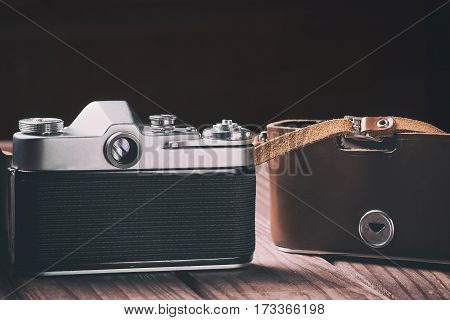 Retro film camera with case on wood and black background. Vintage toned and selective focus.
