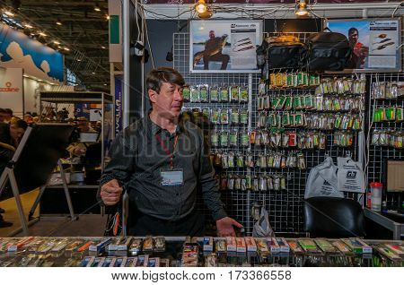 Moscow, Russia - February 25, 2017: Seller of fishing gear on the background with wobblers waiting for buyers