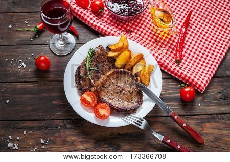 Grilled beef steak seasoned with spices served on a wooden board with fresh cherry tomato baked potatoes and red hot chili peppers.