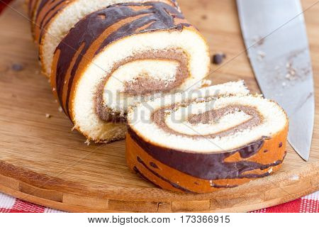 Chocolate Roll Cake On The Wooden Board