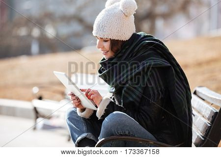 Photo of amazing young lady walking on the street wearing hat and scarf while using tablet computer.