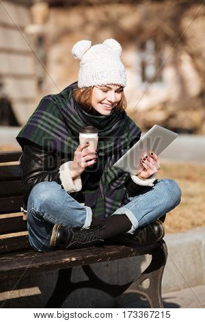 Image of amazing young woman on the street wearing hat and scarf using tablet computer while drinking coffee.