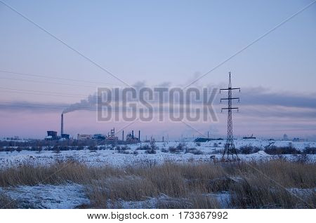 Landscape with an industrial enterprise on the horizon. Winter