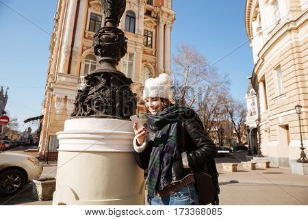 Image of cheerful young lady walking on the street wearing hat and scarf while using mobile phone.