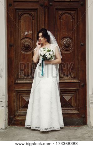 Beautiful, Sensual Brunette Bride In Lace White Wedding Dress Posing With White Roses Bouquet Near O
