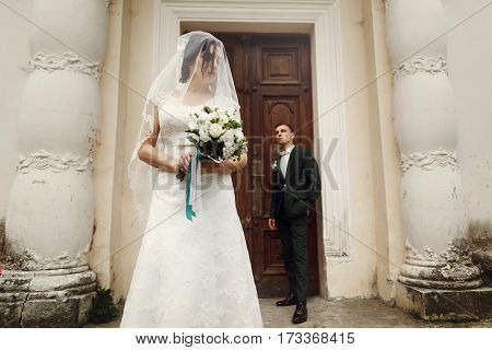 Beautiful Newlywed Brunette Bride Under Veil In White Wedding Dress Posing With Roses Bouquet Near O
