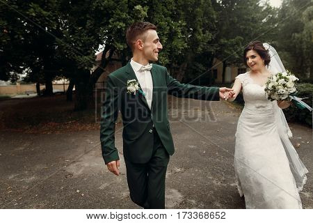 Romantic Couple Of Newlyweds, Handsome Groom In Dark Green Suit And Beautiful Bride In White Dress H