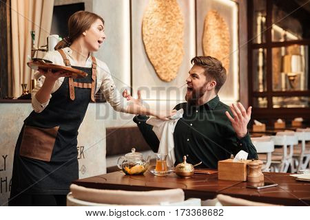 Image of angry screaming bearded young man sitting in cafe. Looking at waiter.