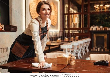 Picture of happy young woman waiter standing in cafe. Looking at camera.