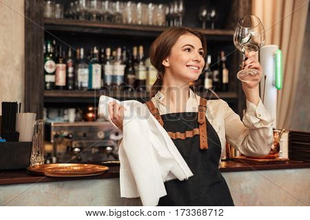 Photo of cheerful young woman standing in cafe wipe a glass. Looking aside.