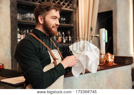 Photo of happy young bearded man bartender standing in cafe. Looking aside and wipe the glass.