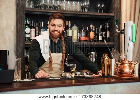 Image of cheerful young bearded man bartender standing in cafe. Looking at camera.