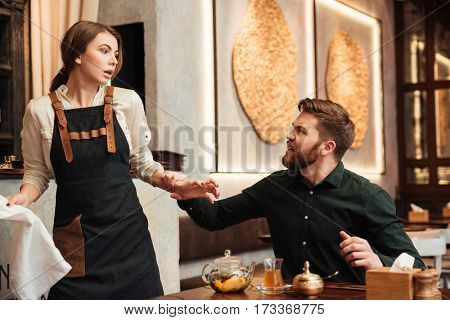 Photo of angry screaming bearded young man sitting in cafe. Looking at waiter.