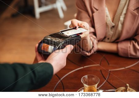 Cropped photo of attractive young pretty woman sitting in cafe. Pays the order with credit card.