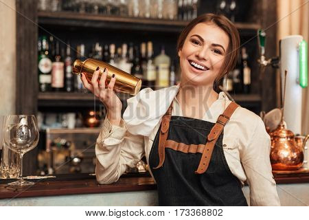 Image of pretty young woman standing in cafe holding shaker. Looking at camera.