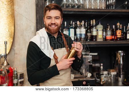 Photo of attractive young bearded man bartender standing in cafe. Looking at camera holding shaker.
