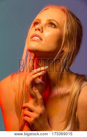 Close up Unusual portrait of woman in singlet which posing in studio and looking up. Vertical image