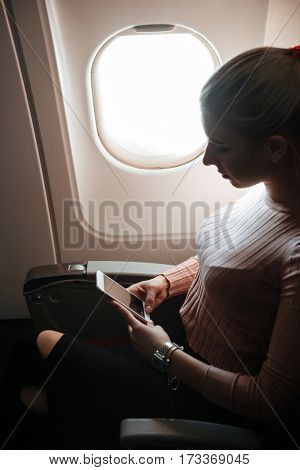 Vertical image of pensive woman which using phone and sitting near the porthole in aircraft. Side view