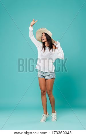 Vertical image of Happy woman in beachwear which waving and looking away. Isolated turquoise background