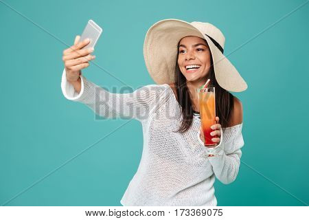 Smiling Woman in beachwear which making selfie on phone and holding cocktail in hand