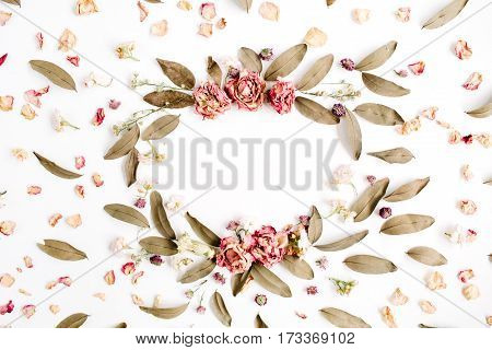 Round frame wreath pattern with roses pink flower buds branches and dried leaves on white background. Flat lay top view. Flower mockup background