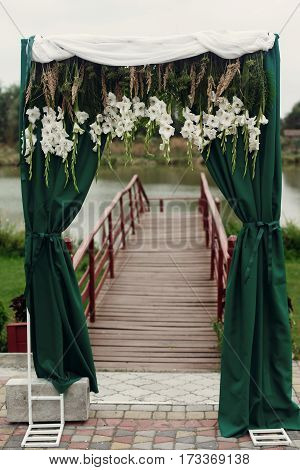 Beautiful Stylish Wedding Aisle Pathway With White Flowers Garland Hanging From Arc With Green Fashi