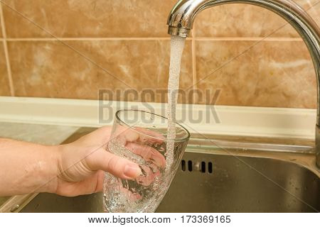 Hand holding a glass of water from the kitchen faucet