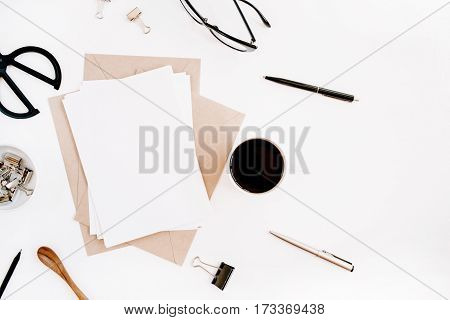 Workspace with clean paper blank coffee craft envelope scissors office supplies on white background. Flat lay top view office table desk.