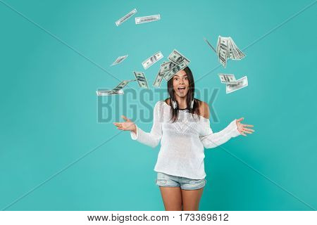 Pretty Woman in beachwear throws the money in studio. Isolated turquoise background