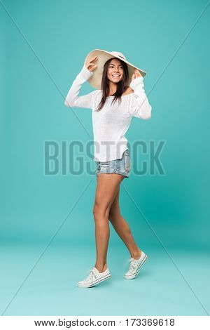 Vertical image of smiling woman in beachwear which holding her hat and looking away. Isolated turquoise background