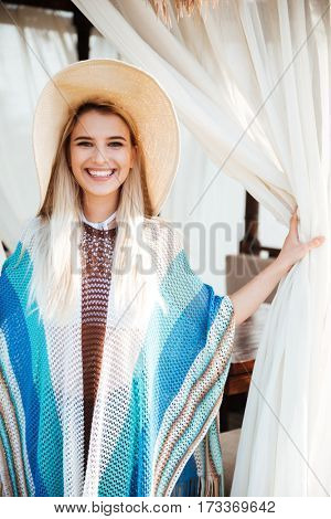 Vertical image of smiling woman in beachwear and hat which posing in alcove and looking at camera