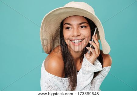 Happy Woman in beachwear which talking on phone and looking away. Isolated turquoise background
