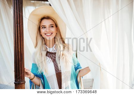 Happy woman in beachwear and hat which posing in alcove and looking away