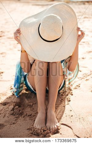 Vertical image of Woman in beachwear and hat which sitting on sand