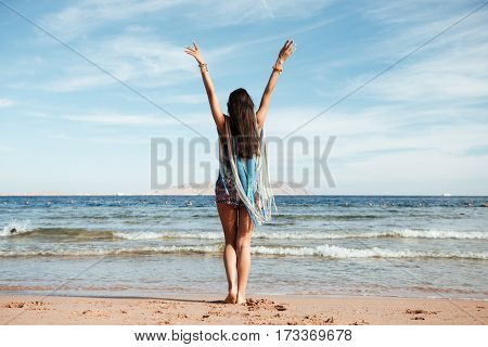 Back view of Woman in beachwear which standing on the beach with hands up