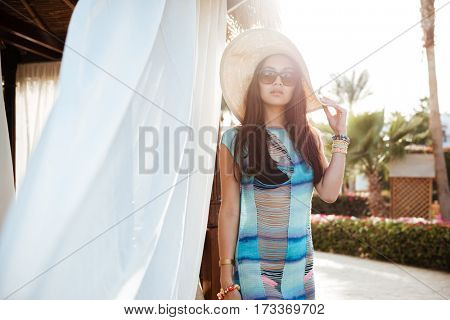 Young Brunette woman in beahwear which posing near the alcove