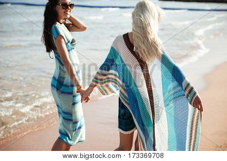 Back view of two girl which holding hands and walking on the beach