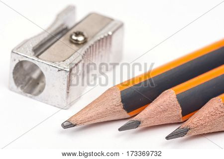 Wooden Pencils With Metal Sharpener Over White Background