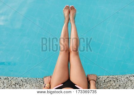 Cropped image of beauty legs of woman which sitting near the pool and holding legs above the water