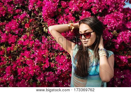 Woman in beachwear and sunglasses which posing near the flower bush
