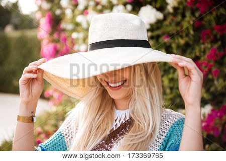 Close-up view of Smiling Woman in hat and beachwear which posing near the flower bush