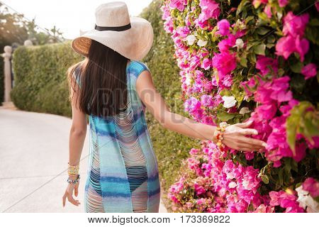 Back view of woman in hat and beachwear which walking near the flower bush