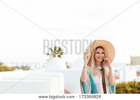 Smiling Blonde woman in beachwear which talking on phone and looking away