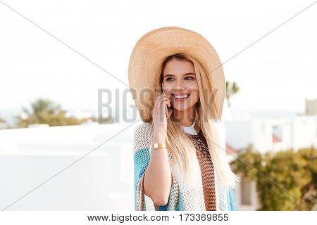 Blonde woman in beachwear which talking on phone and looking away